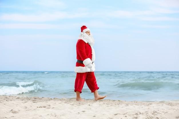 Authentischer weihnachtsmann, der am strand spazieren geht