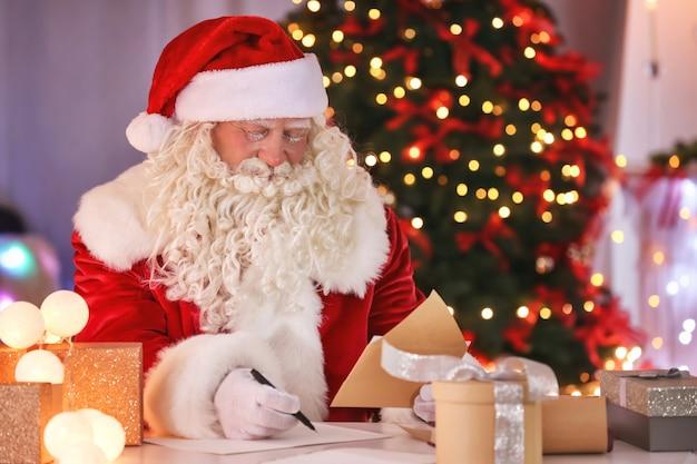 Authentischer weihnachtsmann, der am tisch in einem weihnachtlich dekorierten raum arbeitet