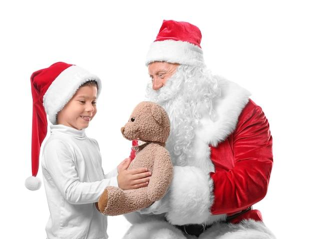 Authentischer weihnachtsmann, der dem süßen jungen in weihnachtsmütze auf weißer oberfläche einen teddybären gibt