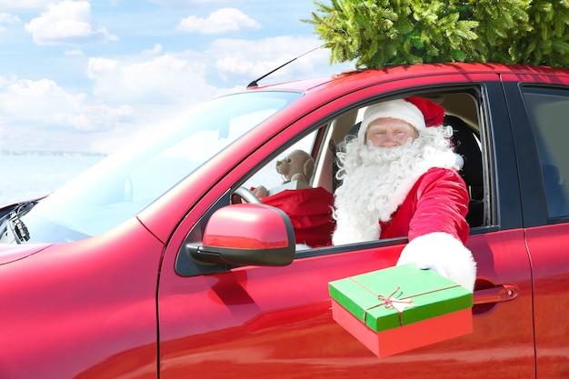 Authentischer weihnachtsmann, der eine geschenkbox hält, während er im auto mit weihnachtsbaum oben sitzt