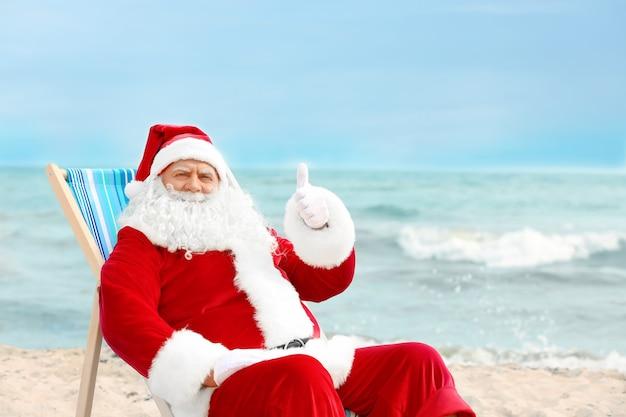 Authentischer weihnachtsmann, der im liegestuhl am strand entspannt