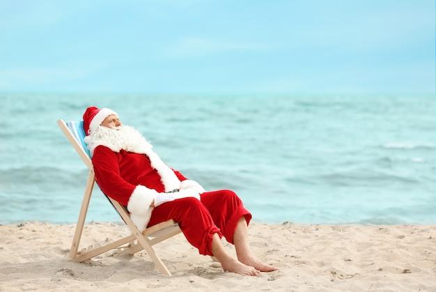 Authentischer weihnachtsmann entspannt im liegestuhl am strand