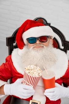 Authentischer weihnachtsmann in den gläsern 3d, die im lehnsessel dösen