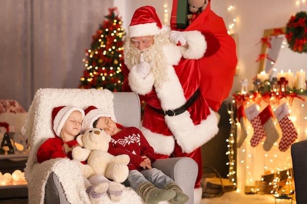 Authentischer weihnachtsmann in der nähe von schlafenden kindern im zimmer mit schöner weihnachtsdekoration