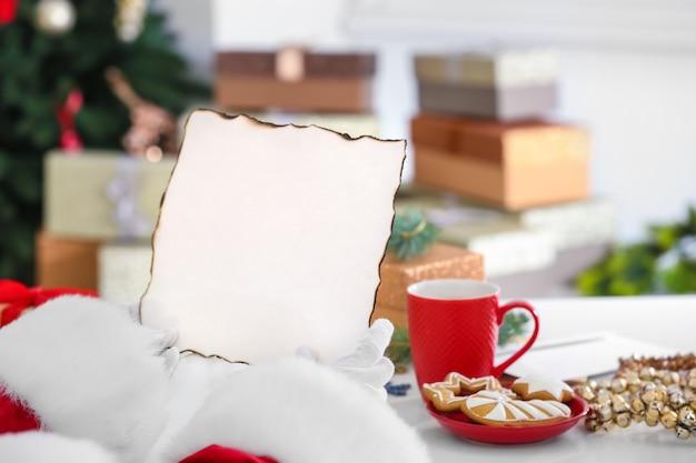 Authentischer weihnachtsmann mit brief am tisch