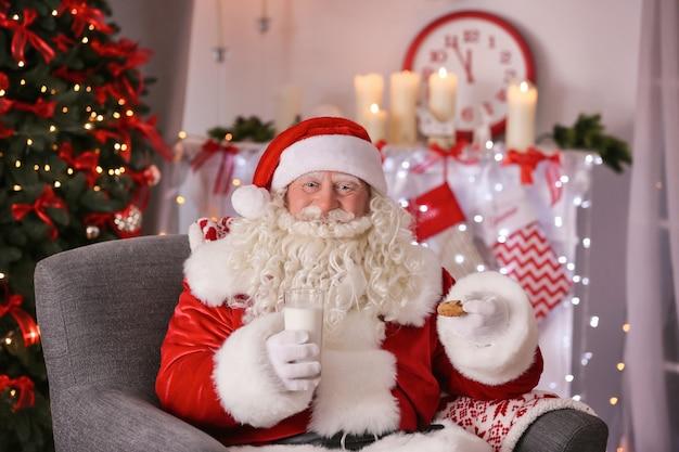 Authentischer weihnachtsmann mit keks und glas milch, die im sessel im raum sitzen, der für weihnachten dekoriert wird
