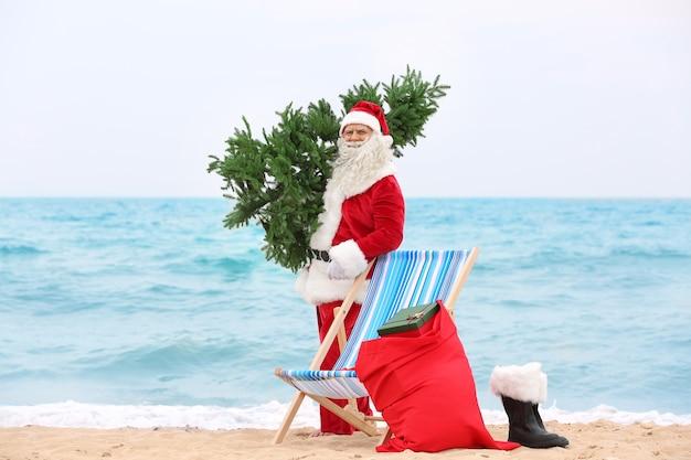 Authentischer weihnachtsmann mit weihnachtsbaum und tasche voller geschenke am strand