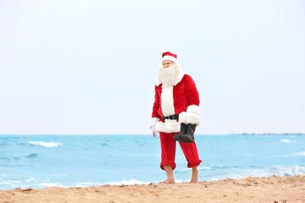 Authentischer weihnachtsmann zu fuß am strand walking