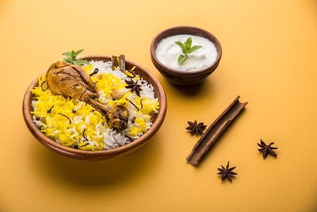 Authentisches chicken biryani serviert in einer schüssel oder auf einem teller auf buntem oder hölzernem hintergrund. es ist ein köstliches rezept aus basmatireis, gemischt mit würzig mariniertem hühnchen, serviert mit salat. selektiver fokus