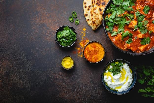 Authentisches indisches gericht chicken tikka masala mit platz für text. würziges curryfleisch in schüssel mit frischem brot naan, joghurt-raita-sauce auf rustikalem dunklem hintergrund, draufsicht, nahaufnahme, kopierraum,