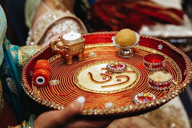 Authentisches indisches tablett mit traditionellen heiligen gegenständen für die hochzeitszeremonie