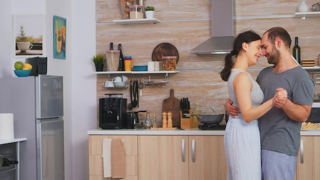 Authentisches paar tanzt langsam beim frühstück in der küche im pyjama. romantischer moment zu zweit, tanz und leidenschaft, intimer, fröhlicher, verspielter morgen für junges ehepaar, das sich umarmt