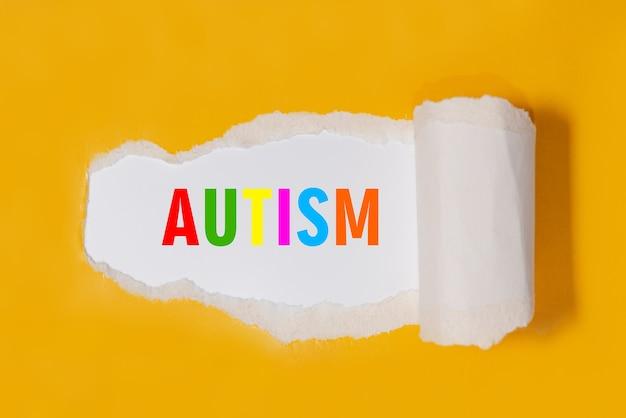 Autismus, wort geschriebene mehrfarbige buchstaben unter zerrissenem gelbem papier. autismus, konzept bild.