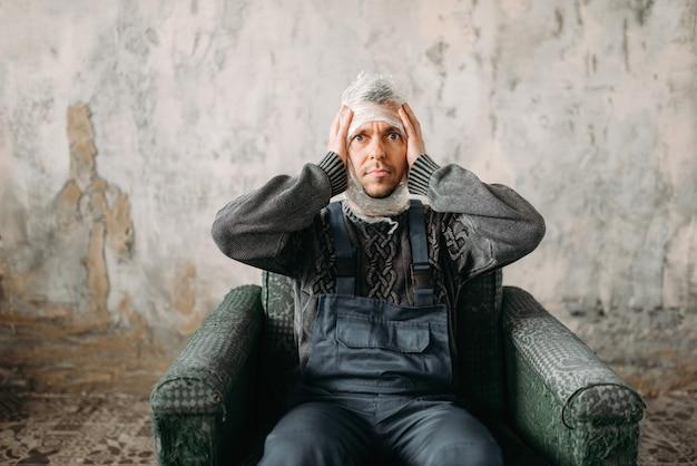 Autist mit stretchfolie auf dem kopf, der auf einem stuhlsyndrom sitzt, innenraum des schmutzraums.