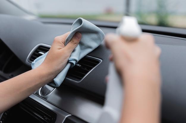 Auto armaturenbrett mit lappen und sprühflasche reinigen