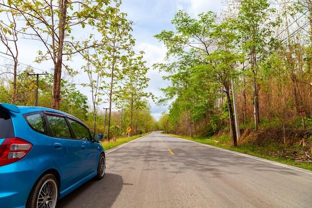 Auto auf asphaltstraße mit berggrünwald transport zum reisekonzept