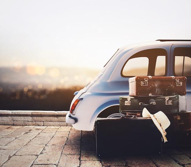 Auto auf der straße bereit für sommerferien während des sonnenuntergangs mit gepäck