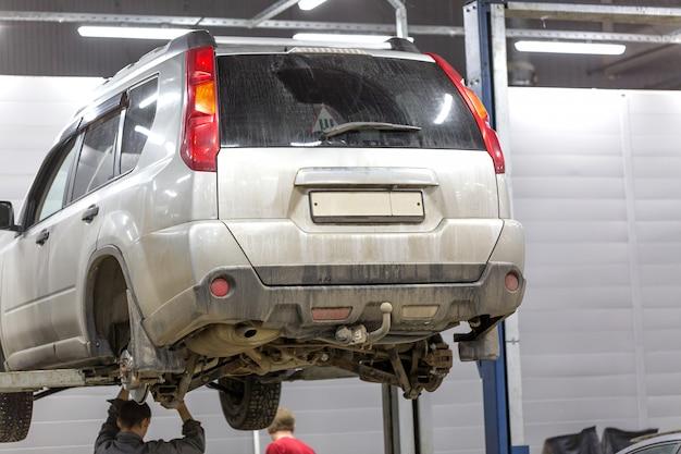 Auto auf einem aufzug in einer reparaturservice-werkstatt