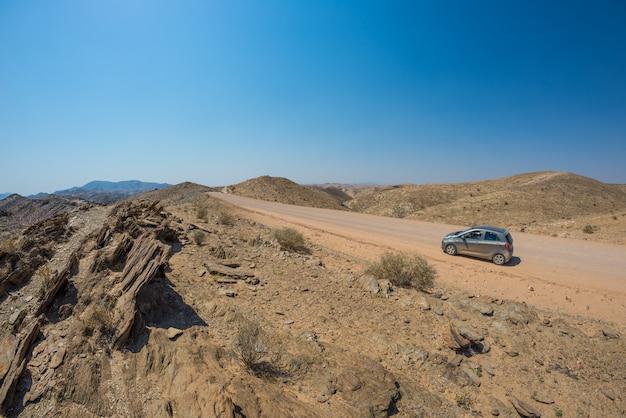 Auto auf schotterstraße in der namibischen wüste