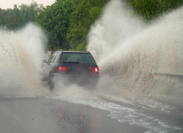 Auto fährt bei starkem regen in große pfütze, wasser spritzt über das auto. autofahren auf asphaltstraße bei gewitter. gefährliche fahrbedingungen