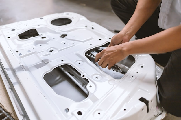 Auto im autoreparatur-service-center-mechaniker, der autotür und karosserielack mit weichzeichner und über licht im hintergrund repariert