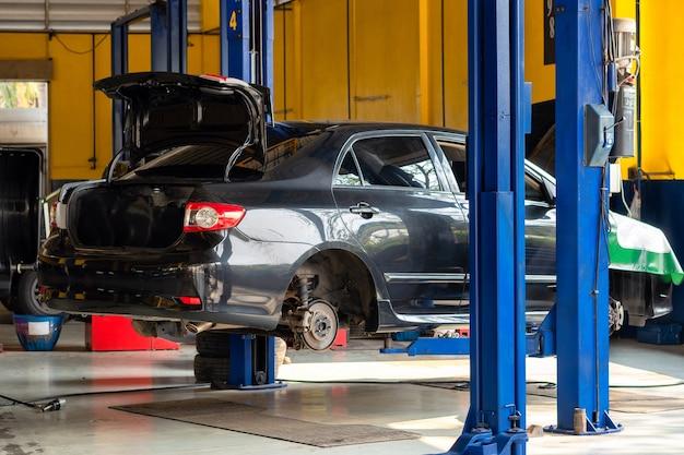 Auto im servicezentrum. fahrzeug angehoben auf einem aufzug. check-up-, wartungs- und reparaturkonzept
