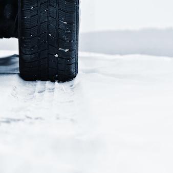 Auto im winter. reifen auf einer verschneiten straße bei schlechtem wetter.