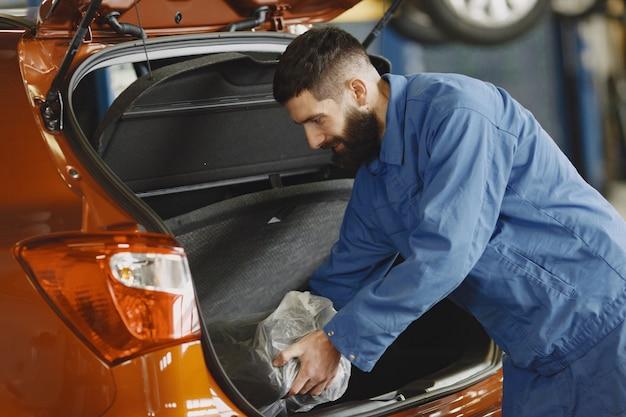 Auto in der garage. mann in arbeitskleidung. schwarzer bart.