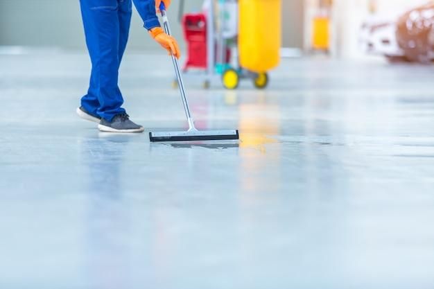 Auto-mechaniker-reparatur-service-center-reinigung mit mopps, um wasser vom epoxidboden zu rollen. in der autoreparaturwerkstatt.