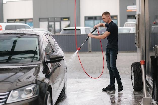 Auto mit aktivschaum reinigen. mann, der sein auto auf selbstautowäsche wäscht.