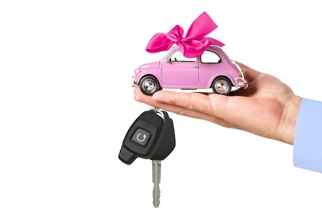 Auto mit bogen und schlüssel auf der hand des händlers lokalisiert auf weißem hintergrund. autokaufkonzept