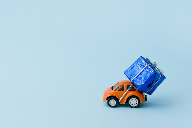 Auto mit geschenkbox auf blauem hintergrund, kopienraum. grußkarte