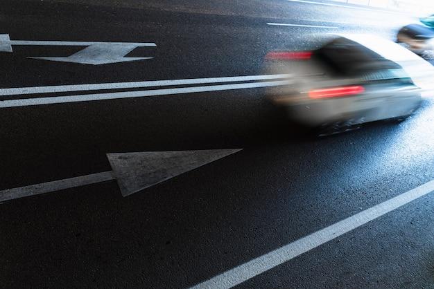 Auto mit geschwungenen kondensstreifen, die mit hoher geschwindigkeit durch das innere eines tunnels fahren.