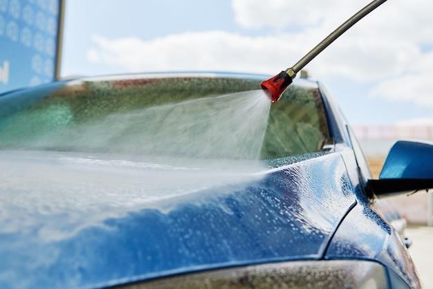 Auto mit hochdruckwasser an der waschanlage reinigen