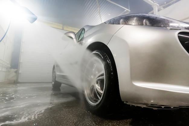 Auto mit hochdruckwasser reinigen. mann, der sein auto unter hochdruckwasser im dienst wäscht. mann arbeiter wäscht das auto. selbstbedienung