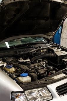 Auto mit offener motorhaube in der autowerkstatt
