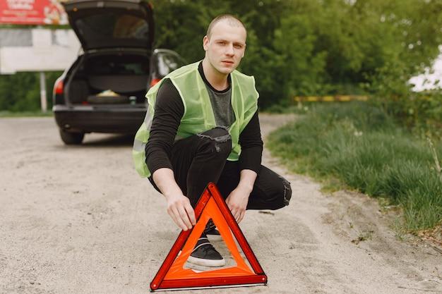 Auto mit problemen und einem roten dreieck, um andere verkehrsteilnehmer zu warnen