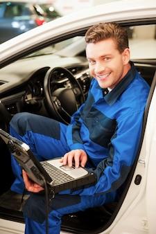 Auto mit speziellem computer untersuchen. selbstbewusster junger mann, der an einem speziellen laptop arbeitet, während er in einem auto in der werkstatt sitzt