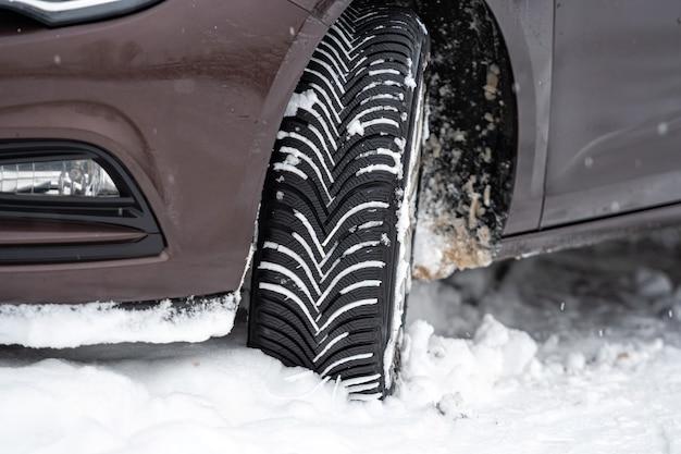 Auto mit winterreifen in der verschneiten straße im freien, reifen im winter auf schnee, nahaufnahme