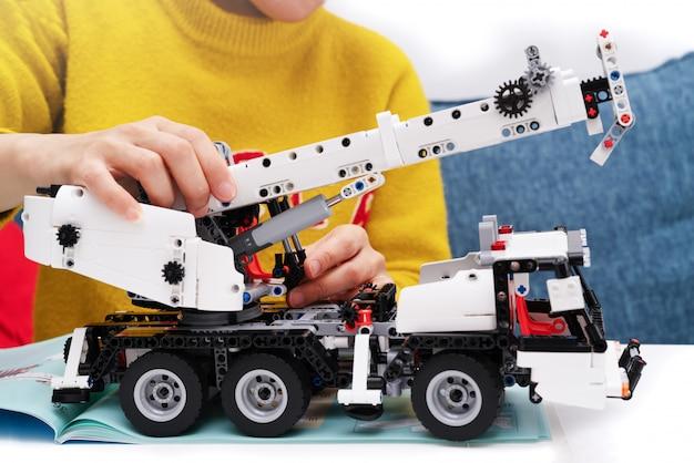 Auto-montagesatz, frau montieren ein sehr kompliziertes und gewöhnliches auto-lkw-spielzeug.