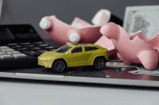 Auto nahaufnahme und dollarnoten mit gebrochenem sparschweinhintergrund. versicherungskonzept.