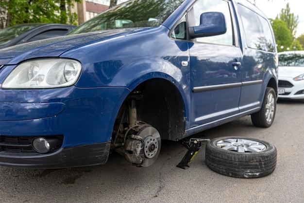 Auto ohne rad und hydraulisch anheben, warten auf reifenwechsel.
