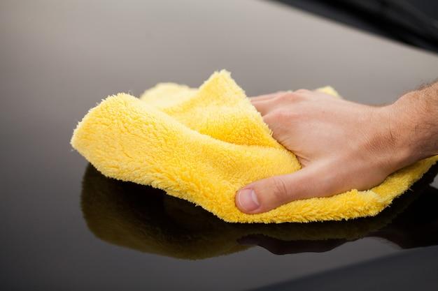 Auto putzen. man hält die mikrofaser in der hand und poliert das auto