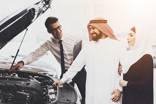 Auto salon familie in muslimischer kleidung und händler