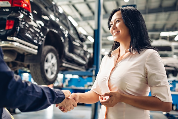 Auto-service-center-szene. der mechaniker händedruck mit dem kunden