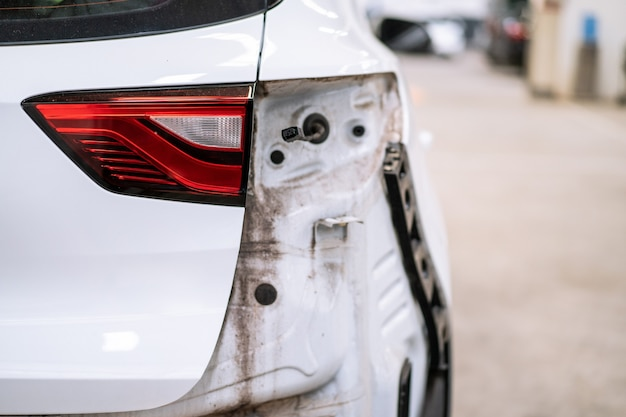 Auto stürzte an der heckkarosserie ab, ein modernes weißes suv-auto wurde hinten beschädigt und in der garage repariert.