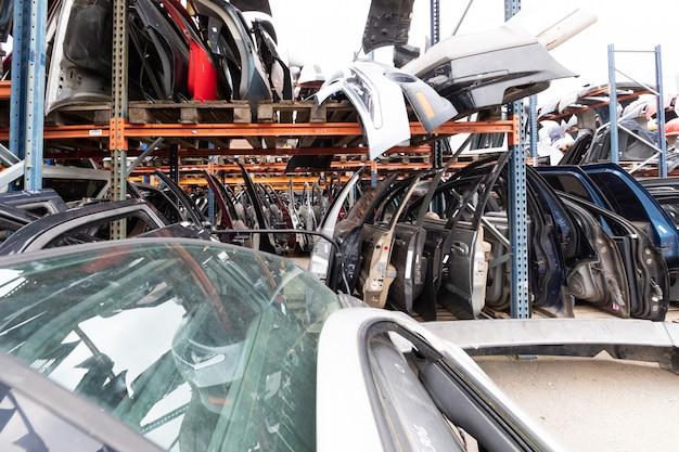 Auto-teile-markt. auf dem boden sind türen, stoßstangen und windschutzscheiben.