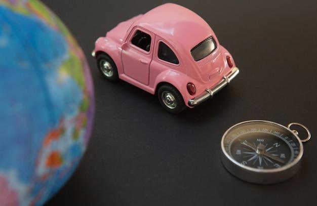 Auto und kugel mit kompaß auf schwarzem