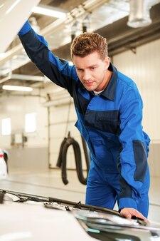 Auto untersuchen. konzentrierter junger mann in uniform untersucht auto beim stehen in der werkstatt