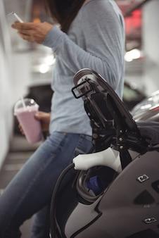Auto wird mit elektroauto-ladegerät aufgeladen, während frau steht